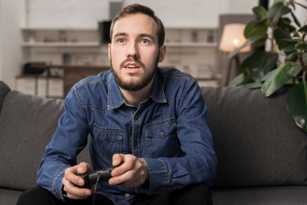 Mężczyzna siedzi na kanapie i trzymając kontroler gier