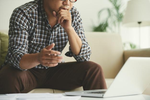 Mężczyzna siedzi na kanapie w domu i patrząc na ekran laptopa