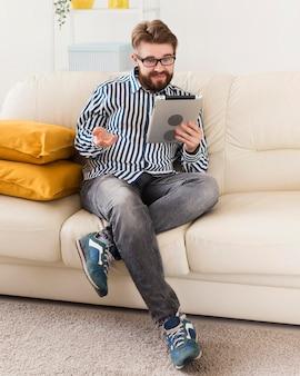 Mężczyzna siedzi na kanapie w domu z tabletem