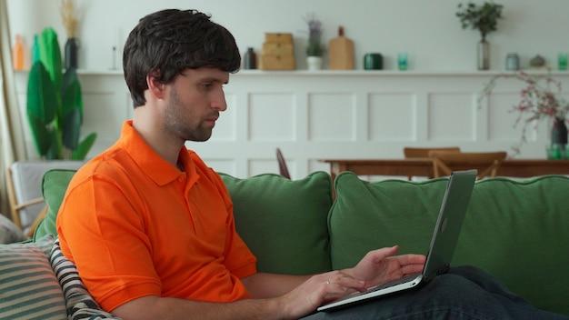 Mężczyzna siedzi na kanapie w domu za pomocą laptopa