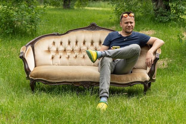 Mężczyzna siedzi na kanapie w ogrodzie