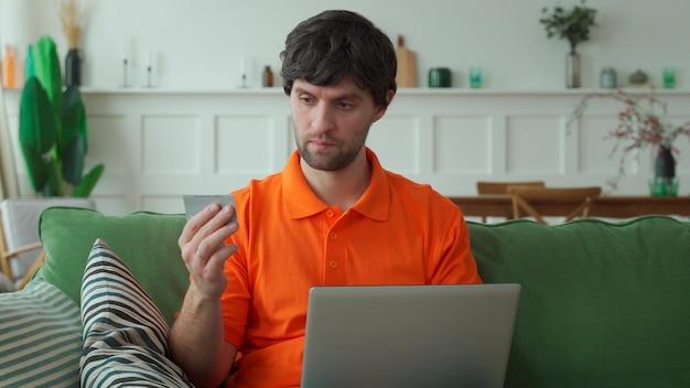 Mężczyzna siedzi na kanapie w salonie z laptopem i kartą kredytową