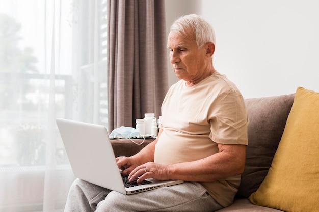 Mężczyzna siedzi na kanapie z laptopem