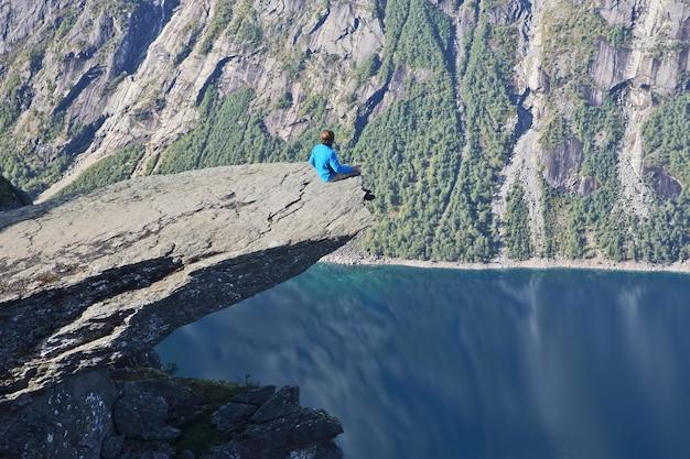 Mężczyzna siedzi na końcu języka trolla. norwegia