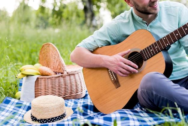 Mężczyzna siedzi na kratę i gra na gitarze