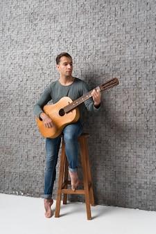 Mężczyzna siedzi na krześle, grając na gitarze klasycznej