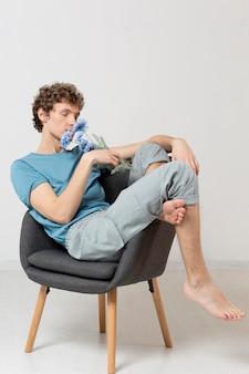 Mężczyzna siedzi na krześle i trzyma kwiaty