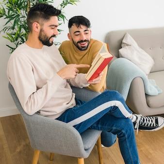 Mężczyzna siedzi na krześle pokazując coś na książki do swojego chłopaka