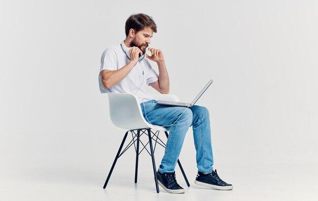 Mężczyzna siedzi na krześle przed laptopem w słuchawkach technologii komunikacji na białym tle. wysokiej jakości zdjęcie