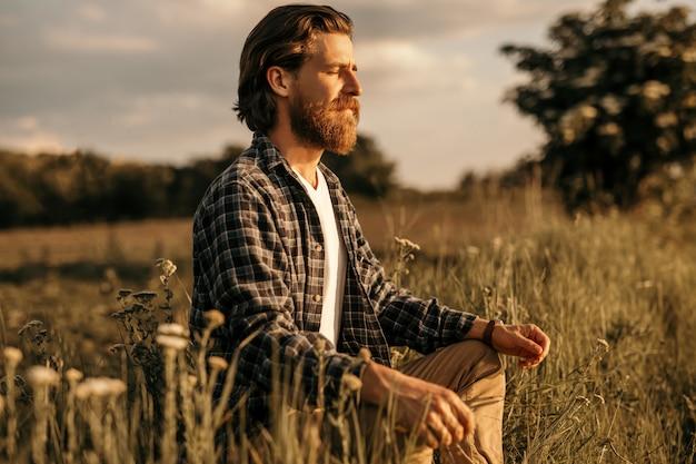 Mężczyzna siedzi na łące i robi ćwiczenia oddechowe