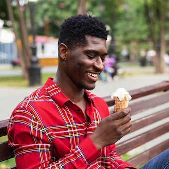 Mężczyzna siedzi na ławce i je lody