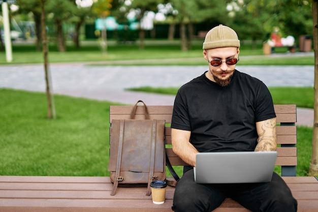 Mężczyzna siedzi na ławce i pracuje na laptopie z wykresami graficznymi, wykresami, diagramami na ekranie handlowców stok