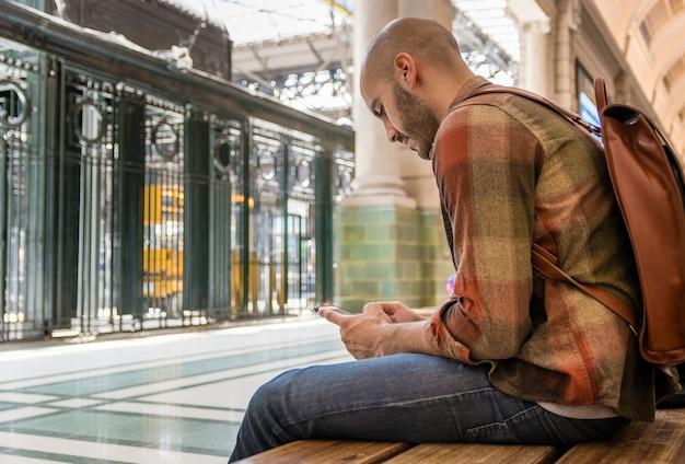 Mężczyzna siedzi na ławce i przy użyciu telefonu komórkowego