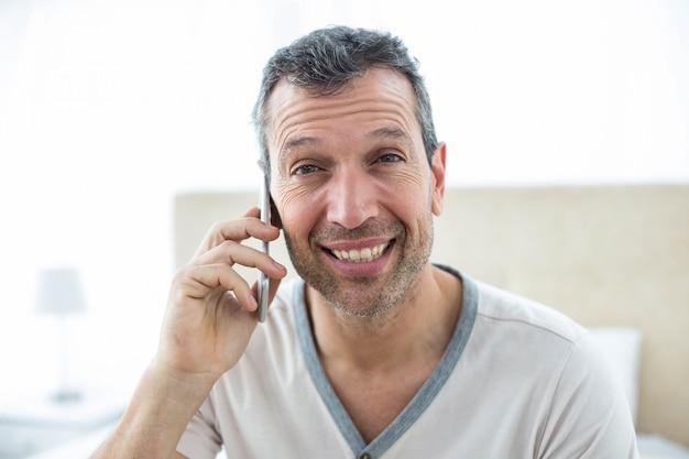 Mężczyzna siedzi na łóżku i rozmawia smartphone w sypialni
