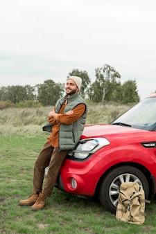 Mężczyzna siedzi na masce samochodu w przyrodzie