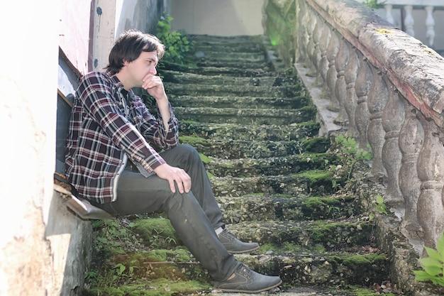 Mężczyzna siedzi na opuszczonym schodach