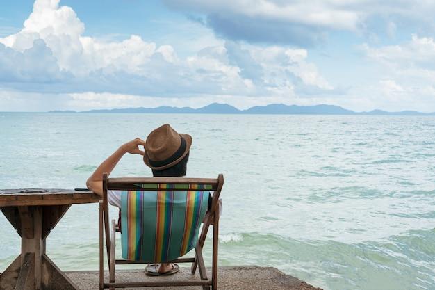Mężczyzna siedzi na plażowym krześle podczas gdy używać telefon komórkowego, kopii przestrzeń.
