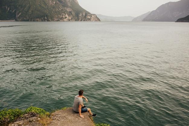Mężczyzna siedzi na plaży lazurowe górskie jezioro.