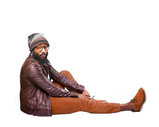Mężczyzna siedzi na podłodze bokiem z jednej nodze rozciągnięty