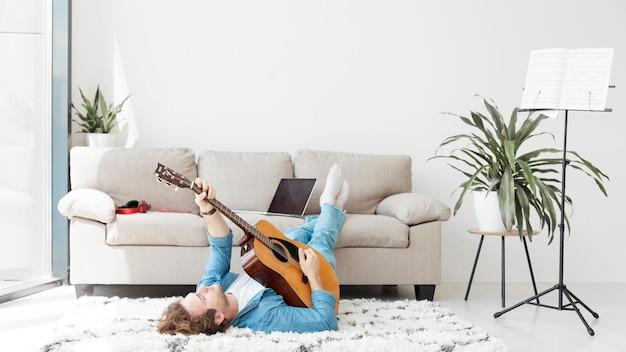 Mężczyzna siedzi na podłodze i gra na gitarze długi widok