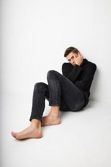 Mężczyzna siedzi na podłodze na białym tle czarna kurtka moda nowoczesne style. wysokiej jakości zdjęcie