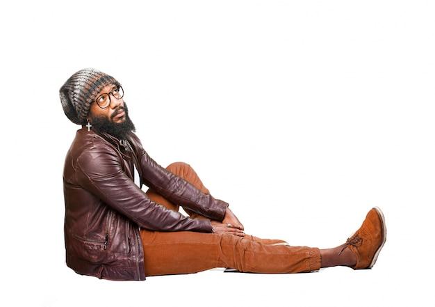 Mężczyzna siedzi na podłodze na boku z jedną nogą rozciągnięty patrząc w niebo