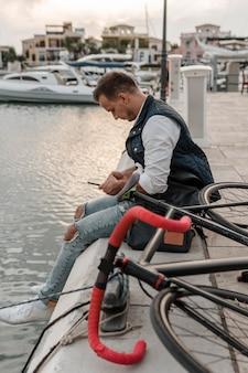 Mężczyzna siedzi na rowerze nad jeziorem