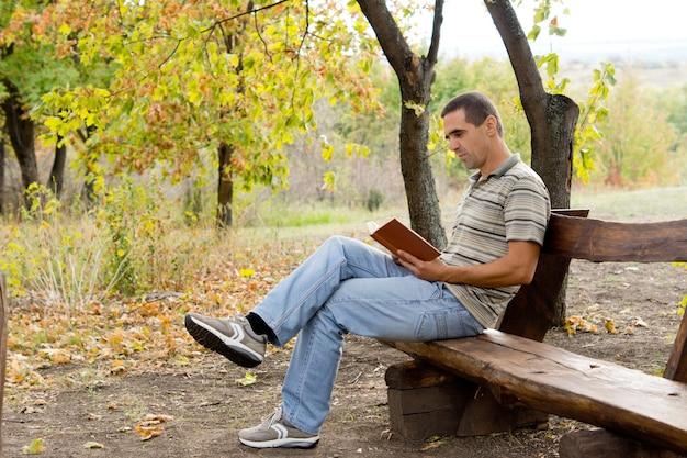 Mężczyzna siedzi na rustykalnej drewnianej ławce, relaks, czytając książkę w kraju w lesie jesienią