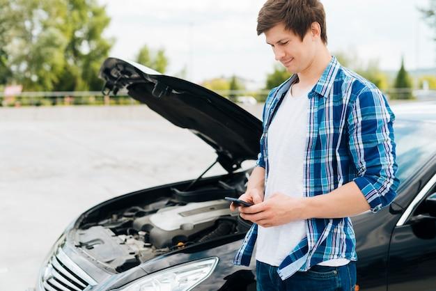 Mężczyzna siedzi na samochodzie i sprawdzanie telefonu