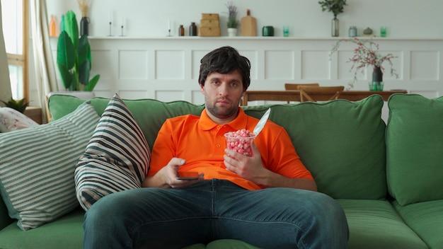 Mężczyzna siedzi na sofie, je popcorn, trzyma pilota i przełącza kanały