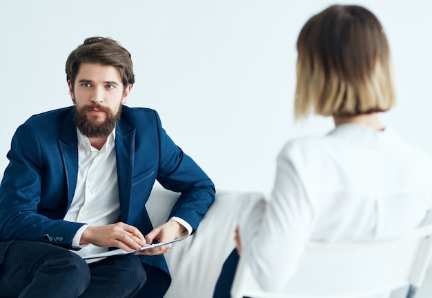 Mężczyzna siedzi na sofie obok pacjenta odwiedzającego psychologa na terapię problemów. zdjęcie wysokiej jakości