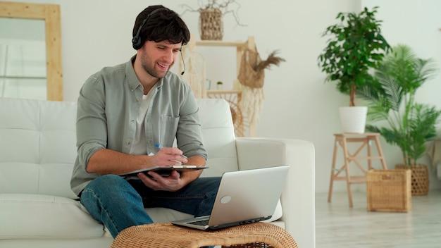 Mężczyzna siedzi na sofie w salonie domu z laptopem i zestawem słuchawkowym i komunikuje się przez łącze wideo.