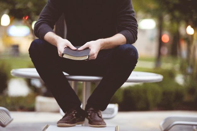 Mężczyzna siedzi na stole w parku i trzymając biblię