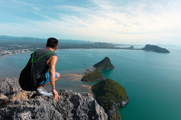 Mężczyzna siedzi na szczycie wzgórza.