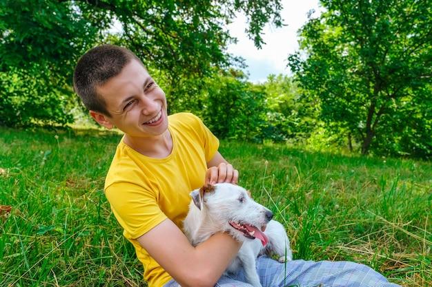 Mężczyzna siedzi na trawie i głaszcze psa jack russell terrier w letnim parku