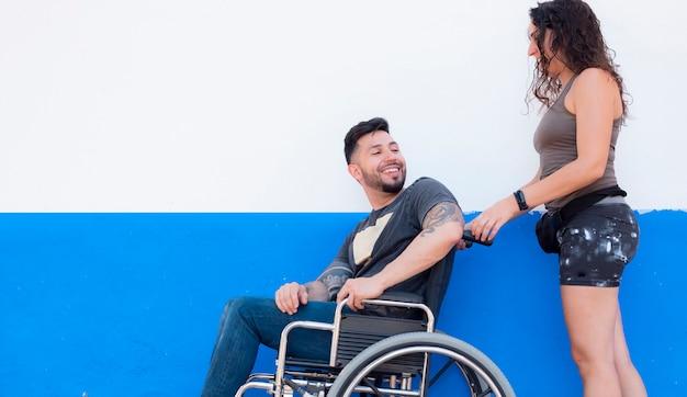 Mężczyzna siedzi na wózku inwalidzkim z dziewczyną
