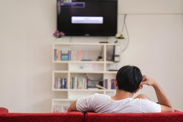 Mężczyzna siedzi napięty. usiądź samotnie na czerwonej kanapie.