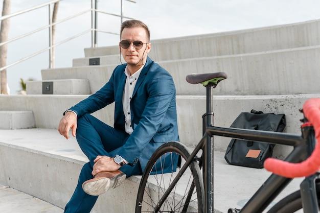 Mężczyzna siedzi obok roweru na zewnątrz z okularami przeciwsłonecznymi