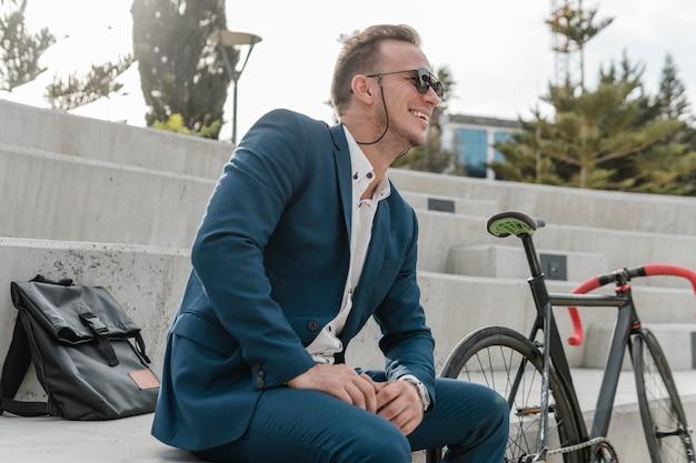 Mężczyzna siedzi obok roweru w okularach przeciwsłonecznych