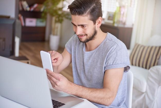 Mężczyzna siedzi przed biurkiem i używa smartfona