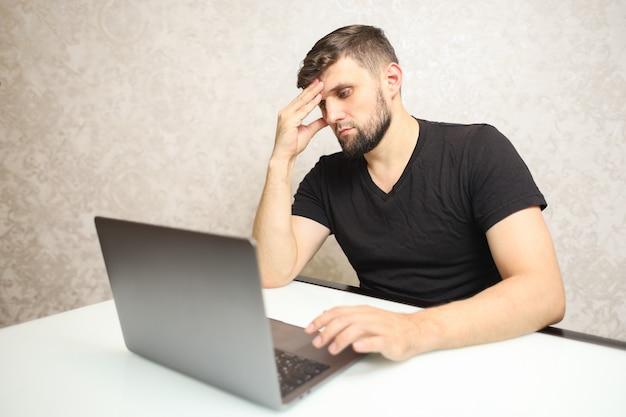 Mężczyzna siedzi przed laptopem