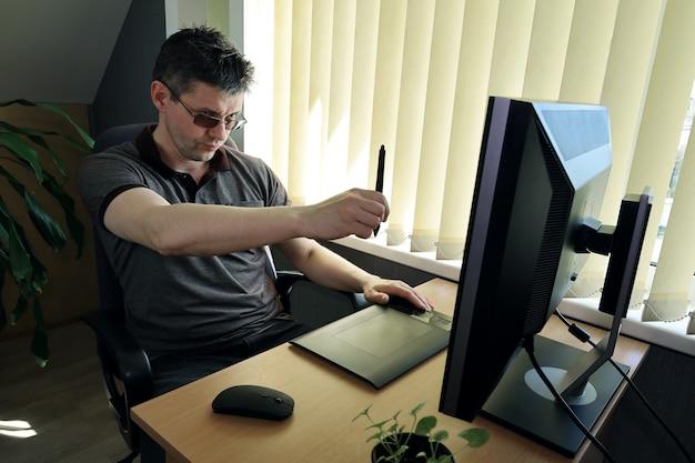 Mężczyzna siedzi przed monitorem i pracuje nad projektem za pomocą tabletu graficznego