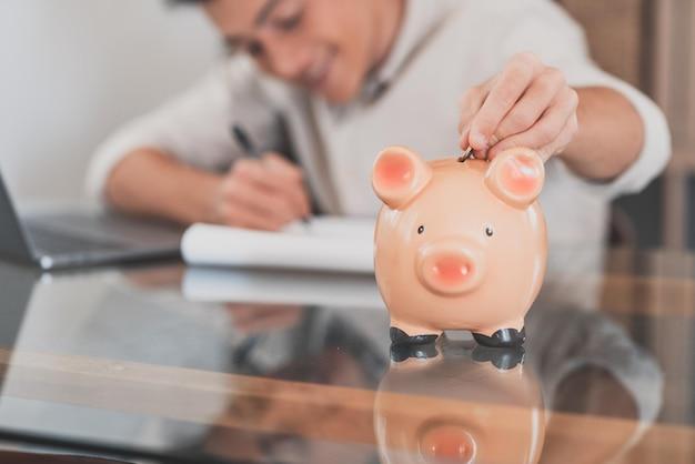 Mężczyzna siedzi przy biurku zarządza wydatkami, oblicza wydatki, płaci rachunki online, korzysta z laptopa, przeprowadza analizę finansów gospodarstwa domowego, skupia się na różowej skarbonce. oszczędzaj pieniądze na przyszłość, bądź ostrożny!