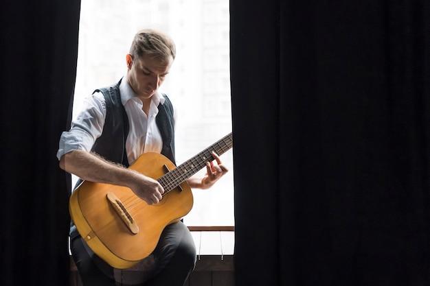 Mężczyzna siedzi przy oknach, grając na gitarze