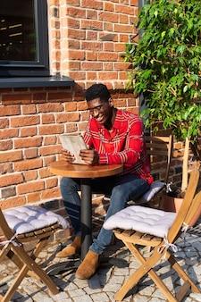 Mężczyzna siedzi przy stole i czyta