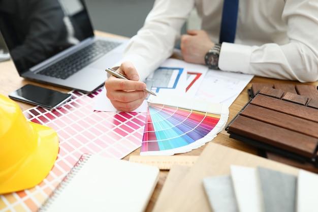 Mężczyzna siedzi przy stole trzymając pióro w dłoniach na stole leży paleta kolorów laptopa smartphone i żółty kask.