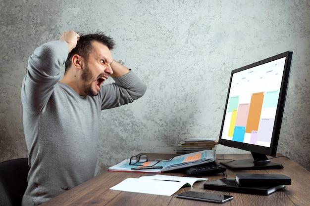 Mężczyzna siedzi przy stole w biurze i krzyczy ze złości