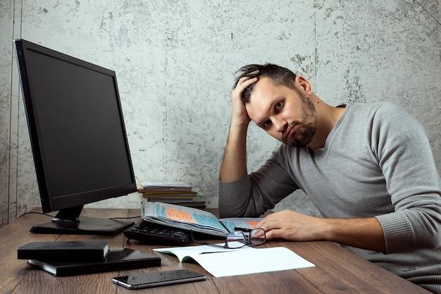 Mężczyzna siedzi przy stole w biurze i nie działa, zmęczony wygląd.
