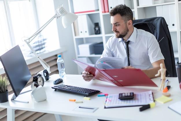 Mężczyzna siedzi przy stole w biurze, pracuje z dokumentami i komputerem.