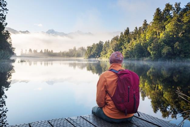 Mężczyzna siedzi swobodnie nad spokojnym jeziorem. pobyt relaksacyjny